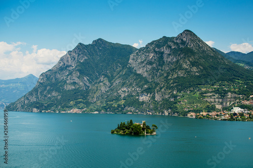 Foto auf Leinwand Blau Loreto island in the middle of the Iseo lake with montains in the background