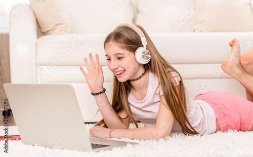 Cuadros en Lienzo Cute teenager girl smiling at her laptop