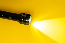 Steel Torch Isolated On Yellow Surface, Producing Light Beams Or Rays, Copy Space B