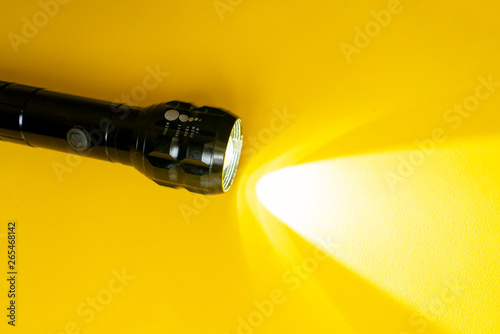 Cuadros en Lienzo steel torch isolated on yellow surface, producing light beams or rays, copy spac