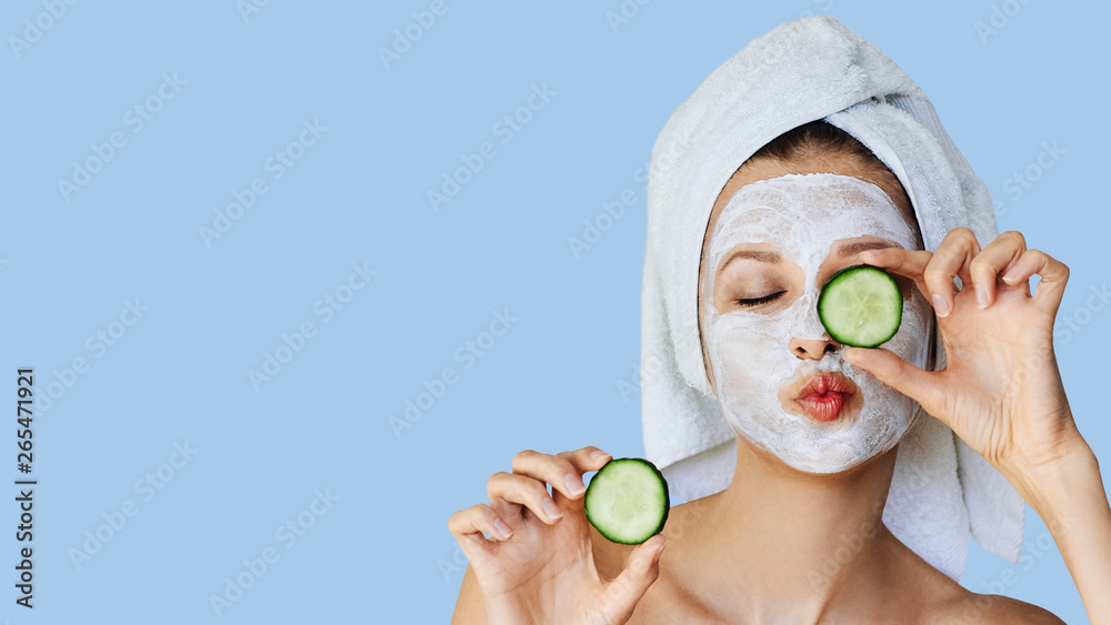 Fototapeta Beautiful young woman with facial mask on her face holding slices of cucumber. Skin care and treatment, spa, natural beauty and cosmetology concept.
