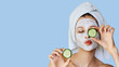 canvas print picture - Beautiful young woman with facial mask on her face holding slices of cucumber. Skin care and treatment, spa, natural beauty and cosmetology concept.
