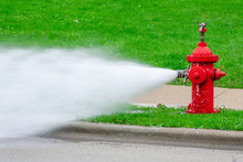 Closeup Of Red Fire Hydrant With High Pressure Spray