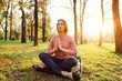 Young woman is meditating in a city park on a sunset background.