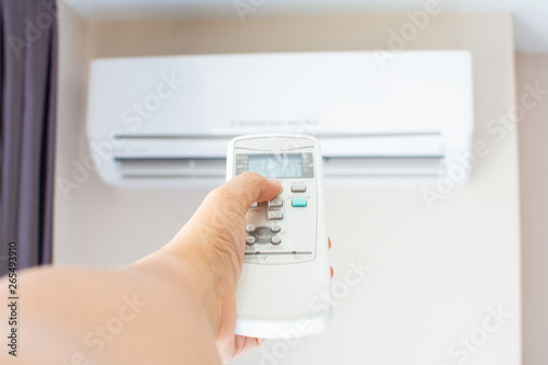 Photo human hand press on remote control of Air Conditioner with hot weather