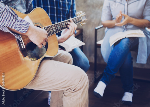 Fotografia, Obraz  Group of  man and woman friends sitting on wooden chair while praise and worship God  by playing guitar and sing a song together in home office, Christian background small fellowship meeting concept