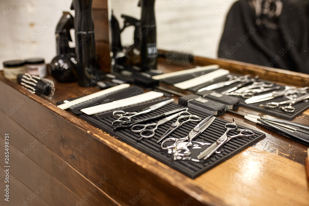 Fototapeta barber tools on wooden shelf and mirror in barbershop