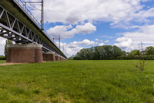 Meadow With A Train Bridge Leading Into Far View. Clouds Over The Horizontal Scenery.