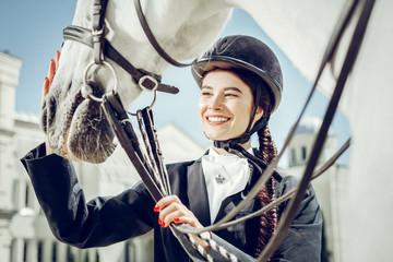Joyful pretty woman looking at her horse