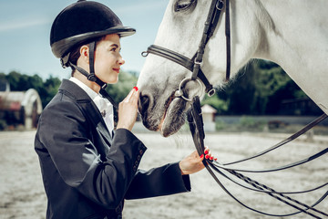 Pleasant young woman touching her horse nose