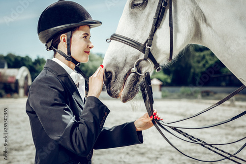 Fototapety, obrazy: Pleasant young woman touching her horse nose
