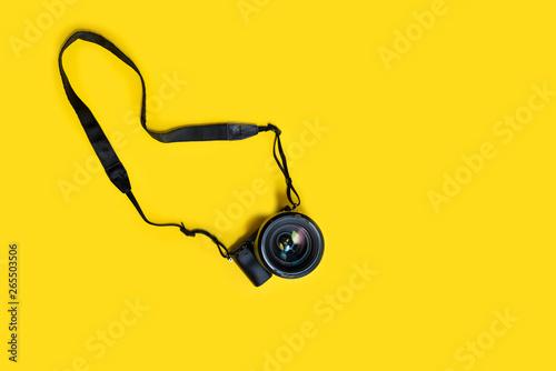 Fototapeta  Mirrorless black camera on yellow background, summer memmories photograher blog