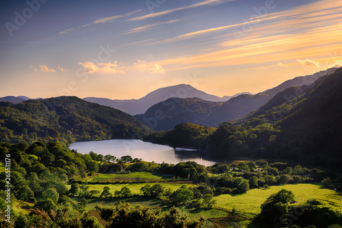 The Sun shining across a mountain and into Llyn Gwynant, Snowdonia (Eryri), Wales (Cymru), UK