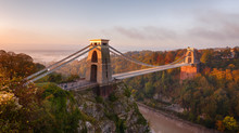 Clifton Suspension Bridge On An Autumn Morning As The Sun Rises And Breaks Through The Clouds