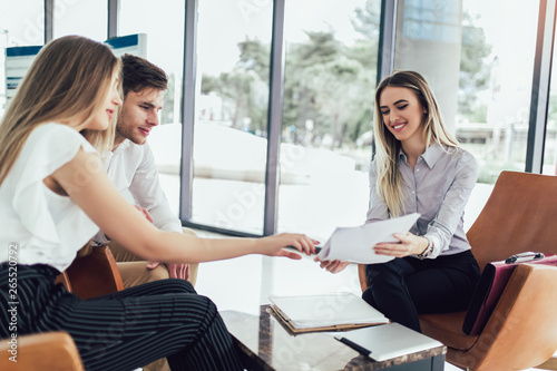 Photo Financial advisor showing report to young couple for their investment