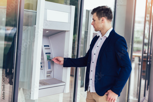 Fototapeta Young business man using ATM