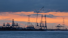 Riverbank With Silhouettes Of Container Terminal Cranes During Orange Colored Sunset, Port Of Antwerp, Belgium.