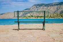Metal Green Bench On The Waterfront With Sea And Mountain View