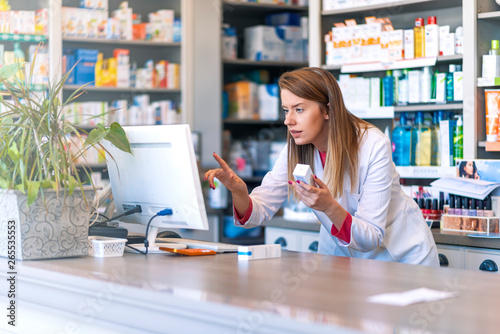 Fotobehang Apotheek Portrait of pharmacist standing at counter in pharmacy. Pharmacist using the computer at the pharmacy. Medicine, healthcare and technology concept