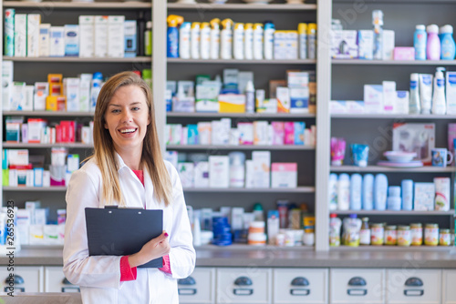 Photo sur Toile Pharmacie Hospital pharmacist worker. Portrait of cheerful smiling female pharmacist in pharmacy drugstore. Female pharmacists working in warehouse depot. Pharmacist posing chemist's shop