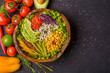 Wooden bowl with chickpea, avocado, wild rice, quinoa, tomatoes, greens, cabbage, lettuce on dark stone background. Vegetarian superfood. Top view with copy space.