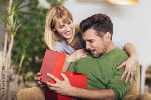 Happy man receiving a present from his girlfriend while sitting on the sofa Canvas Print