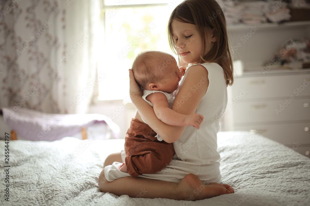 Fototapety, obrazy: older sister kisses baby for 1 month, embraces