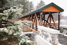 Covered Wooden Bridge Across A River On A Snowy Day.