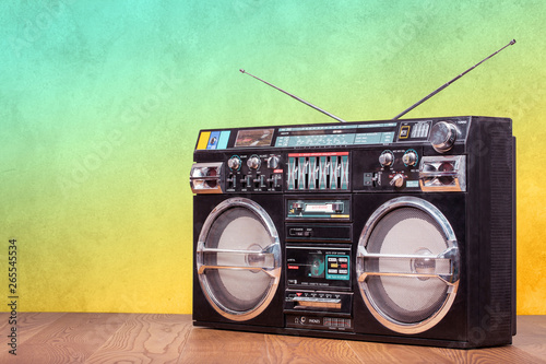 Photo Retro boombox ghetto blaster outdated portable radio receiver with cassette recorder from 80s front gradient colored wall background