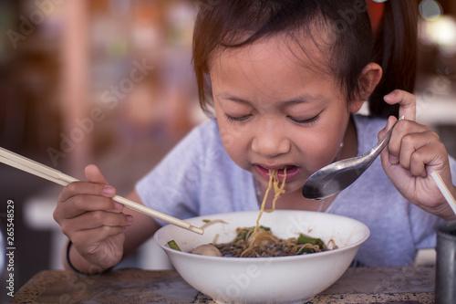 Foto op Canvas Kruidenierswinkel Asian child girl eating noodles with chopstick in restaurant
