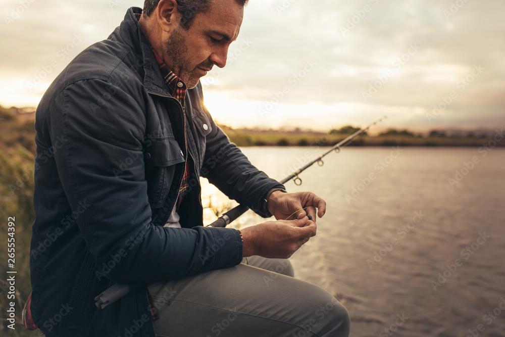 Fototapety, obrazy: Man sitting near a lake with fishing rod