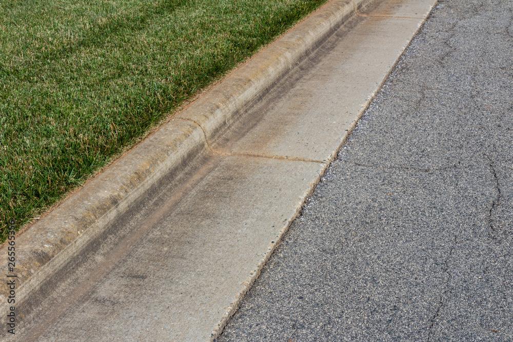 Fototapeta Angled view formed concrete curb, green grass and asphalt street, horizontal aspect
