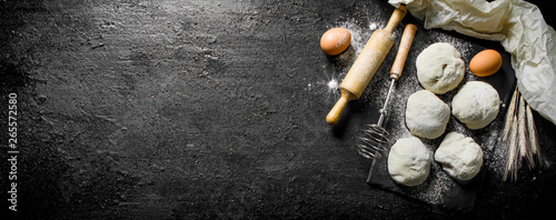 Round pieces of dough with eggs and rolling pin. Fototapeta