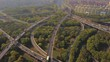 Aerial view of cars on highway junctions with green trees. Bridge roads or streets in structure of architecture and transportation concept. Top view. Urban city, Shanghai at noon, China.