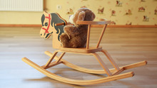 Toy Teddy Bear Sitting On Wooden Rocking Horse On Brown Wood Texture Laminate Floor Indoors On Yellow Patterned Wall Background. Childhood Concept.