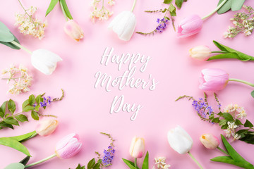 Happy mothers day concept. Top view of pink tulip flowers in frame with happy mothers day text on pink pastel background. Flat lay.