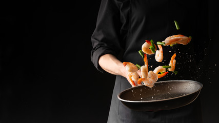 Seafood, Professional cook prepares shrimps with sprigg beans. Cooking seafood, healthy vegetarian food and food on a dark background. Horizontal view. Eastern kitchen