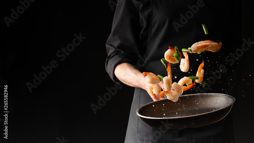 Fotobehang Eten Seafood, Professional cook prepares shrimps with sprigg beans. Cooking seafood, healthy vegetarian food and food on a dark background. Horizontal view. Eastern kitchen