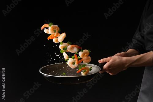 Fotografie, Obraz  Sea food, cooking shrimp with herbs, on a dark background, horizontal photo, hea