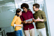 Leinwandbild Motiv Multiethnic business team using a digital tablet in the office of small startup company