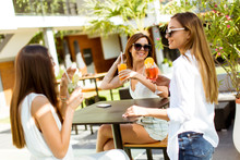 Young Women Drinking Coctail A...