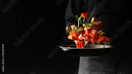 Fototapeta Chef prepares pieces of salmon or trout fillet with green beans in a pan, on a black background for design, recipe book, menu, restaurant or hotel sign, cooking, gastronomy obraz