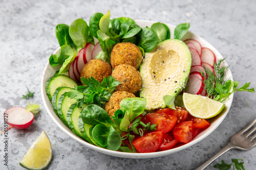 Photo  salad with avocado, falafel,cucumber, tomato and redish, healthy vegan lunch bow