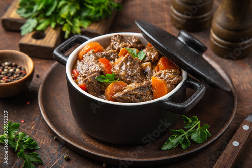 Fotografia beef stew with vegetables in black pot on dark wooden background,