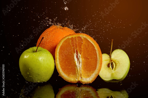 Poster Fruits Apples and oranges fruits with drops and splashes of water on a black background