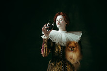 Wanna Try. Medieval Redhead Young Woman In Golden Vintage Clothing As A Duchess Holding Puppy And Glass With Red Wine On Dark Green Background. Concept Of Comparison Of Eras, Modernity And Renaissance