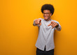 canvas print picture - Young african american man over an orange wall cheerful and smiling pointing to front