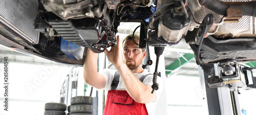 Fotomural  Automechaniker in Werkstatt repariert Fahrzeug // car mechanic in work clothes w