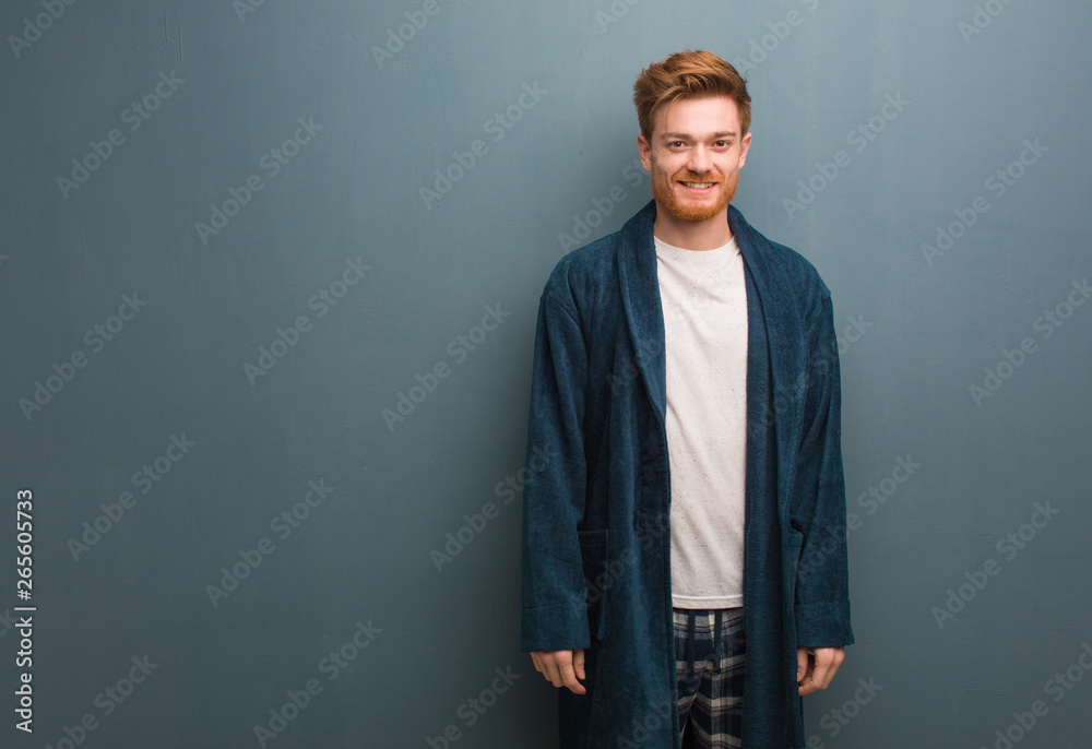 Fototapeta Young redhead man in pajama cheerful with a big smile