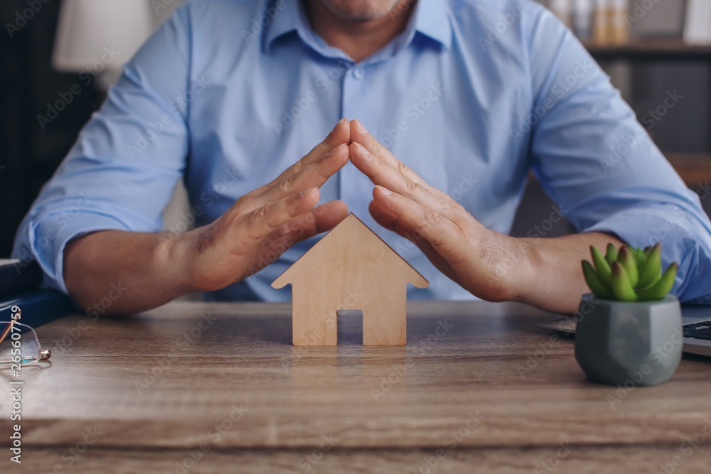 Fototapeta Male insurance agent with figure of house at table, closeup